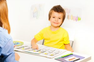 Smiling boy plays in developing game pointing at colorful cards of days and activities on calendar with his parent sitting opposite at the table